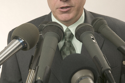 Man Speaking Into Microphones